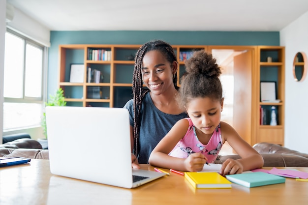 Mother helping and supporting her daughter with online school while staying at home. new normal lifestyle concept. monoparental concept.