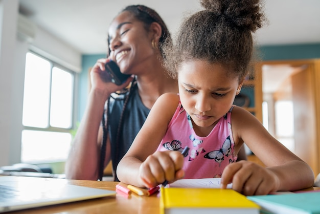 Mother helping and supporting her daughter with online school while talking on the phone at home. new normal lifestyle concept. monoparental concept.