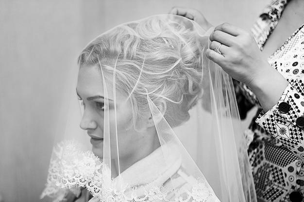 若い美しい花嫁が結婚式のために服を着るのを手伝っている母。白黒写真