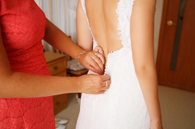Мать помогает молодой красивой невесте одеться для свадебной церемонии