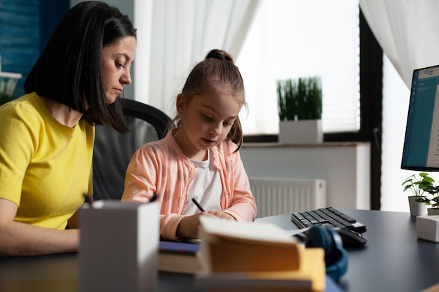 Mother helping young daughter with school homework