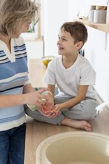 어머니는 아이가 그의 손을 씻는 것을 돕는다