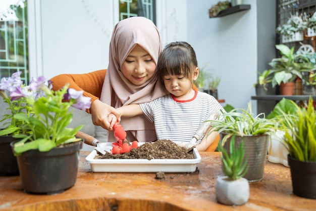 Mother helps her daughter hold a small shovel to take the soil in the tray
