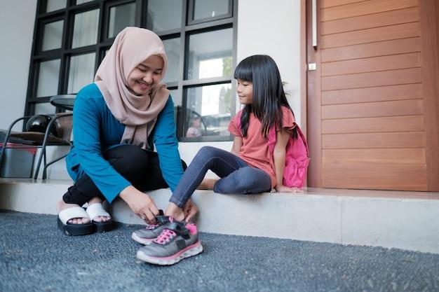 母は娘が学校に行く準備をしている間、朝に靴を履くのを手伝います