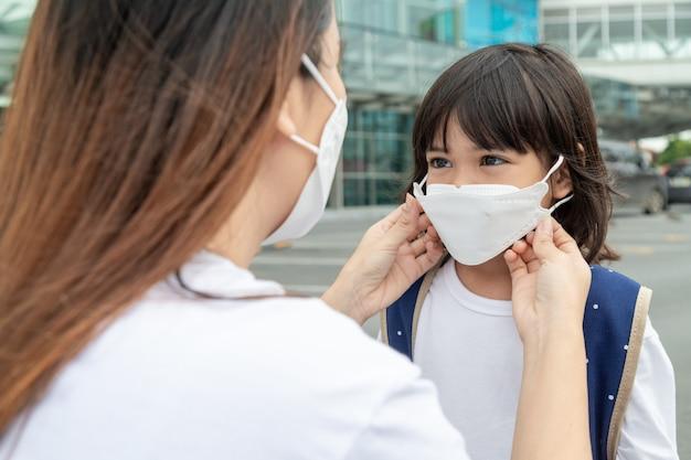 어머니는 covid19 발병을 보호하기 위해 의료용 마스크를 쓴 딸을 돕습니다