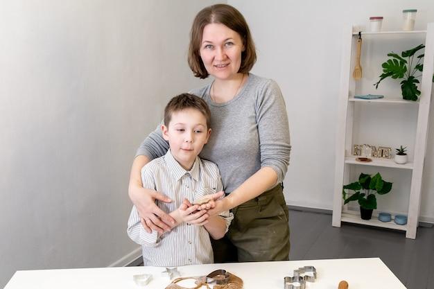 Мать помогает сыну испечь печенье к празднику