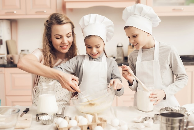 Mother helps kids to mix ingredients for dough.
