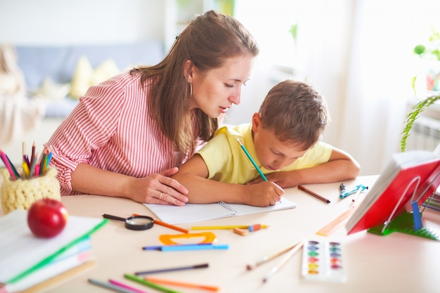 Mother helps son to do lessons.