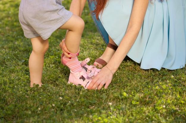 Мать помогает ребенку носить обувь