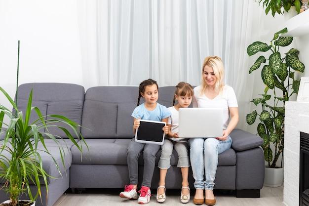 母親は、2人の娘が勉強するときにタブレットとラップトップを使用して、オンラインで勉強するのを手伝っています。