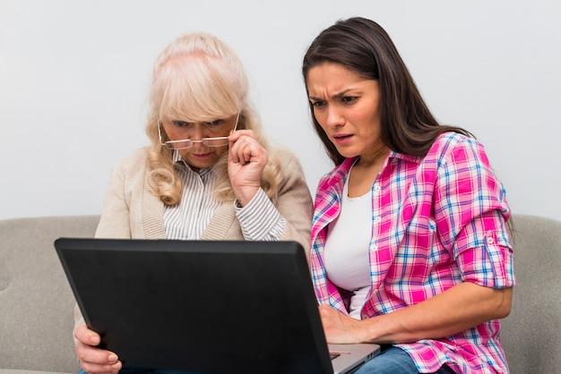 Madre e figlia adulta guardando portatile con curiosità