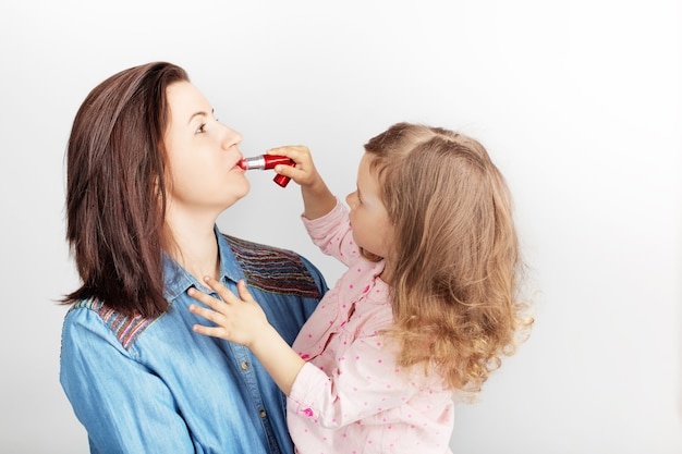 Mother and her child daughter girl with a lipstick