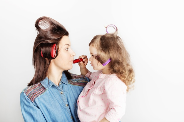 Mother and her child daughter with a lipstick
