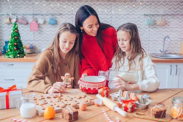 Mother and her cute daughters cooking christmas cookies