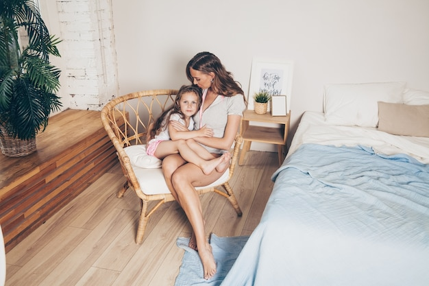 Mother and her cute preschool daughter child girl in pajamas hugging sitting in a wicker chair in the morning.