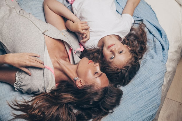 Mother and her cute preschool daughter child girl in pajamas playing and hugging in bed in the morning top view.