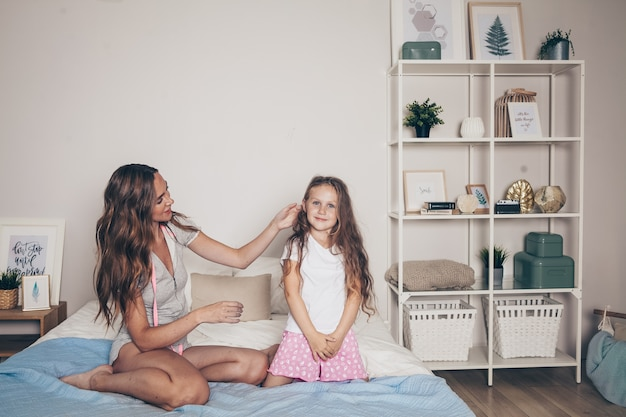 Mother and her cute preschool daughter in pajamas