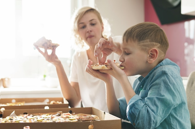 Mother and her cute son eating delicious italian pizza at home