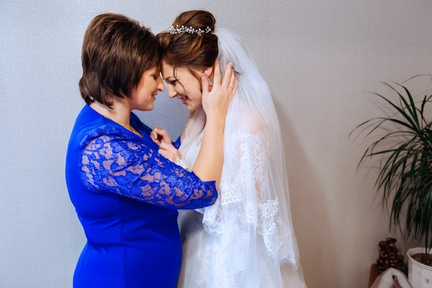 Mother and her daughter the bride stands face to face against the wall
