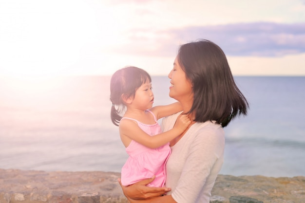 Mother and her daughter child girl playing and hugging on sea background in evening