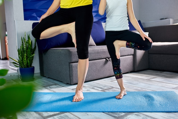 Mother and her daughter doing yoga together at home.