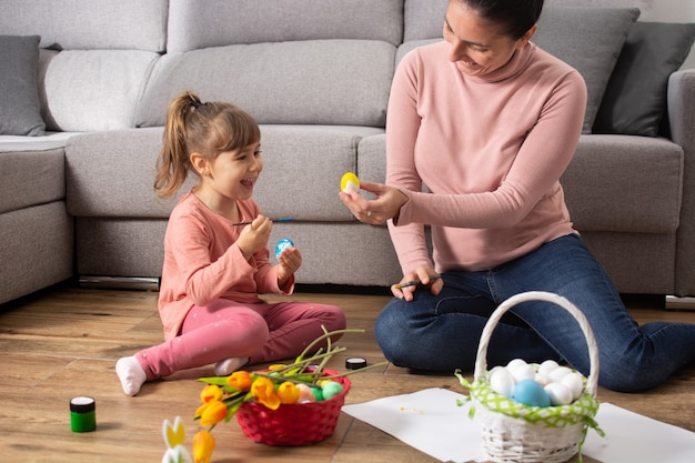 A mother and her daughter painting easter eggs at home.