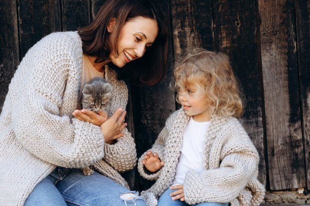 Mother and her daughter play with a little cat by the wooden wall.