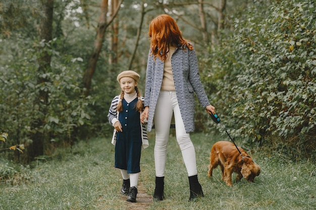 Mother and her daughter playing with dog. family in autumn park. pet, domestic animal and lifestyle concept. autumn time.