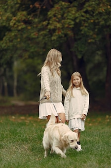 Mother and her daughter playing with dog. family in autumn park. pet, domestic animal and lifestyle concept