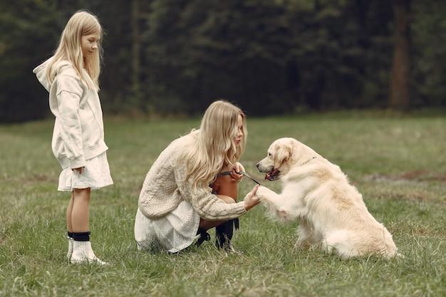 Madre e figlia che giocano con il cane. famiglia nella sosta di autunno. pet, animali domestici e concetto di stile di vita