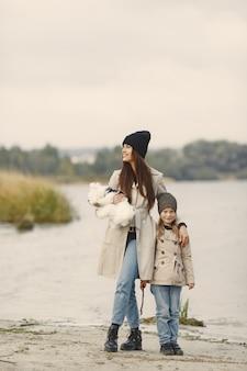 Madre e figlia che giocano con il cane. pet, animali domestici e concetto di stile di vita