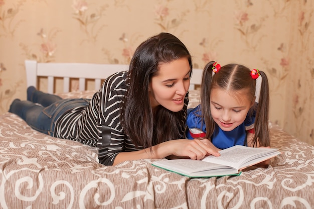 Mother and her daughter reading a book.