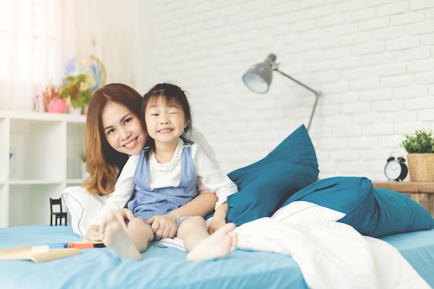 Mother and her daughter relexing on the bed at home.