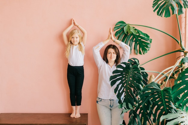 Mother and her daughter standing in yoga pose over pink wall in studio.