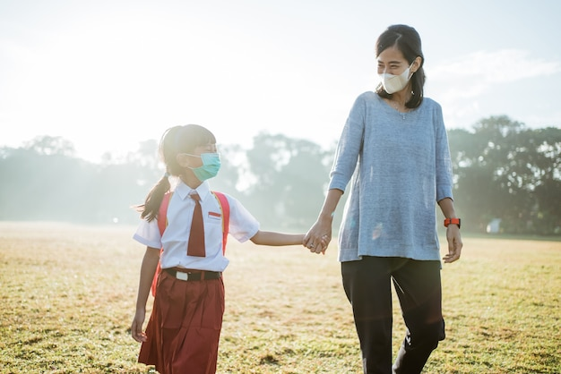 Mother and her daughter walking together and wear face mask
