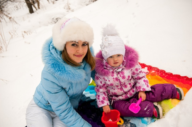 Mother and her little daughter enjoying beautiful winter day outdoors.