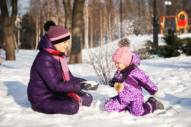 Mother and her little daughter enjoying beautiful winter day