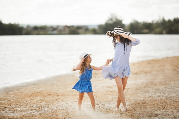 Mother and her little daughter having fun at the coast. young pretty mom and her child playing near the water