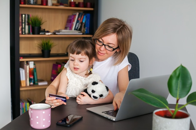 Mother and her little daughter holding a credit card. shopping online concept.