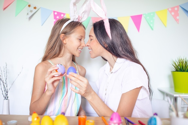 Mother and her little daughter painting eggs. happy family preparing for easter.