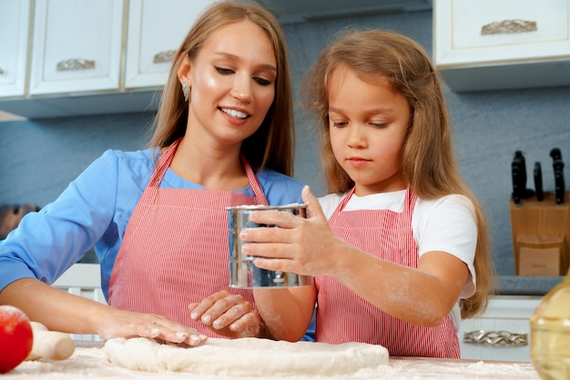 Mother and her little daughter preparing dough in kitchen