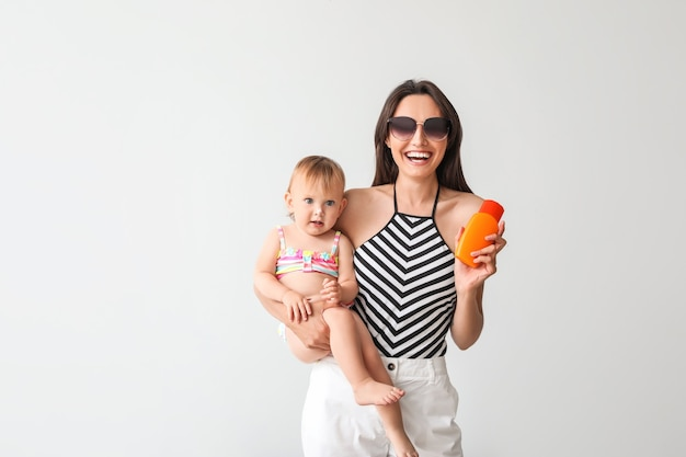 Mother and her little daughter with sunscreen cream on grey