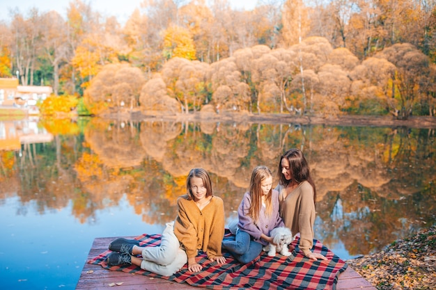 Mother and her little daughters in autumn on picnic on the lake