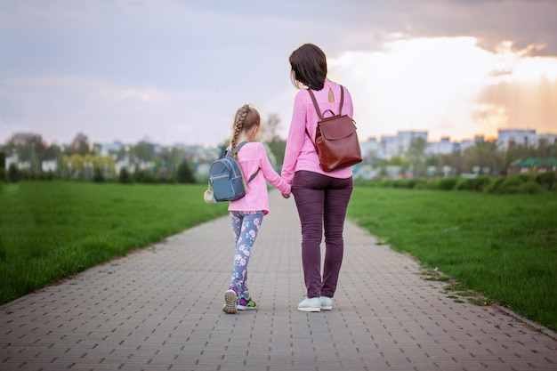 Mother and her little dauther with backpack walking in summer day. view from a back.