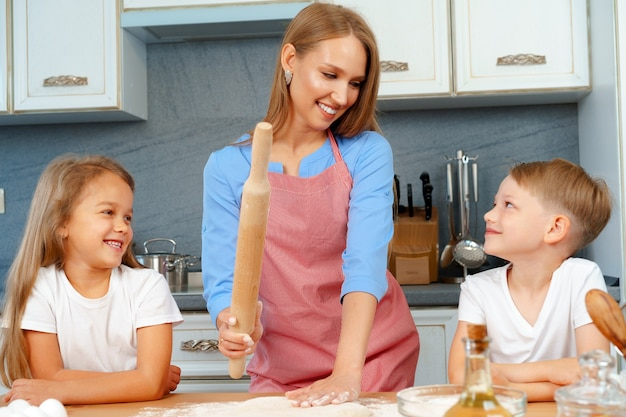 Mother and her little kids, boy and girl, helping her to prepare dough
