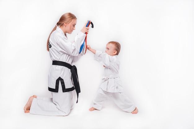 白で武道を練習している彼女の幼い息子の母