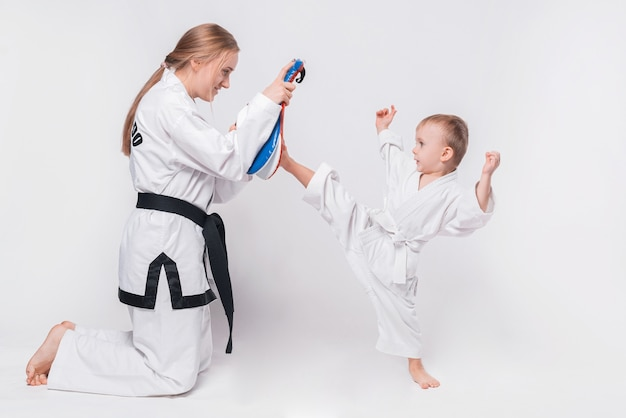 Mother her little son practicing martial arts on white