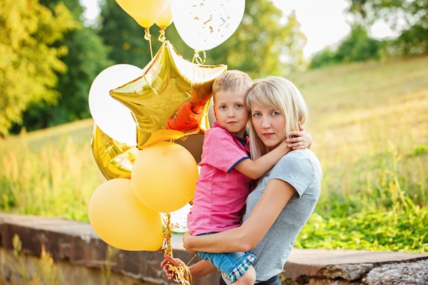 Mother and her little son with gold balloons in summer day.