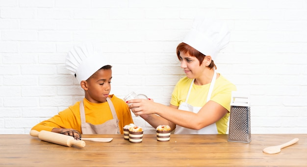 Mother and her son dressed as chef in a kitchen