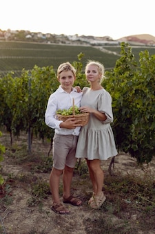 Mother and her teenage son are standing in a vineyard with a wicker basket and green grapes in nature